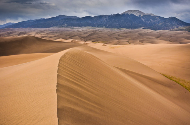 A vast expanse of sand dunes ends at a chain of mountains on a stormy day.
